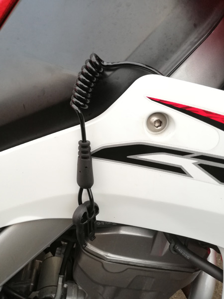 無限電光hit-air用伸縮ワイヤーをHonda CRF250Lのタンク下フレームに取り付けてサイドカウルから出したところ。ワイヤーはフレームのサイドカウル取付け部突起の下側を通している。