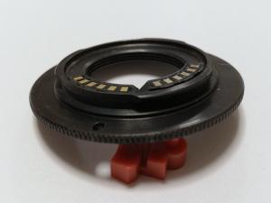 【写真1】Gfotoの薄型Cマウントレンズ→Nikon1ボディ用マウントアダプターに交換用の薄型チップ(左側)を載せてみたところ。チップの正規の位置は右側。厚みと出っ張りを比較するためにチップを並べた。